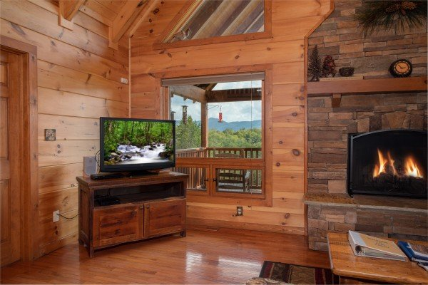 Living room with a television, fireplace, and mountain views at Cedar Creeks, a 2-bedroom cabin rental located near Douglas Lake