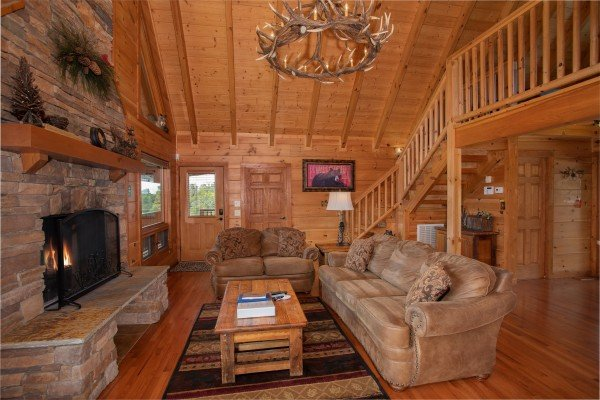 Couch, sofa, fireplace, and custom chandelier in the living room at Cedar Creeks, a 2-bedroom cabin rental located near Douglas Lake