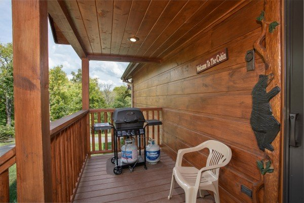 Propane grill on a covered deck with custom black bear decor at Cedar Creeks, a 2-bedroom cabin rental located near Douglas Lake