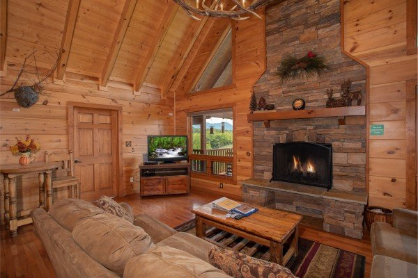 A vaulted living room with fireplace and television at Cedar Creeks, a 2-bedroom cabin rental located near Douglas Lake