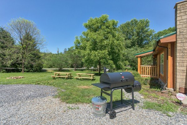 Charcoal grill and picnic tables in the yard at Grill & Chill, a 2-bedroom Gatlinburg cabin rental