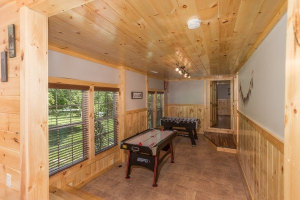 Air hockey and foosball tables in a game room at Grill & Chill, a 2-bedroom Gatlinburg cabin rental