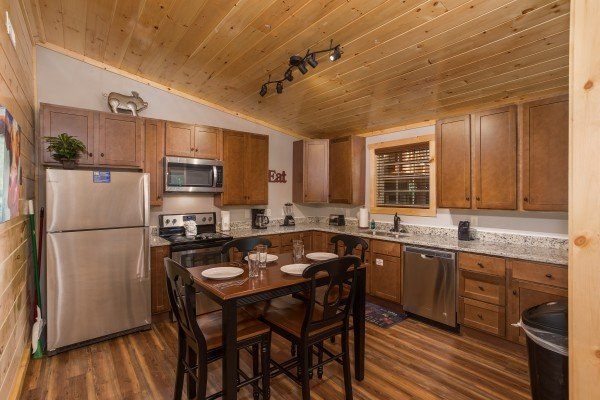 Kitchen with stainless steel appliances and seating for four at Grill & Chill, a 2-bedroom Gatlinburg cabin rental
