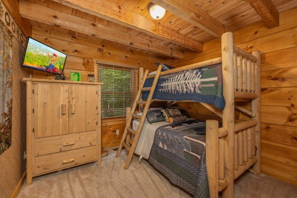 Bunk beds, dresser, and TV in a bedroom at Sweet Caroline, a 2 bedroom cabin rental located in Pigeon Forge