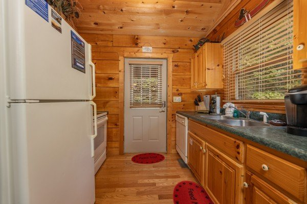 Galley kitchen with white appliances at Sweet Caroline, a 2 bedroom cabin rental located in Pigeon Forge
