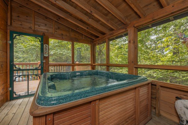 Hot tub on a screened in porch at Sweet Caroline, a 2 bedroom cabin rental located in Pigeon Forge