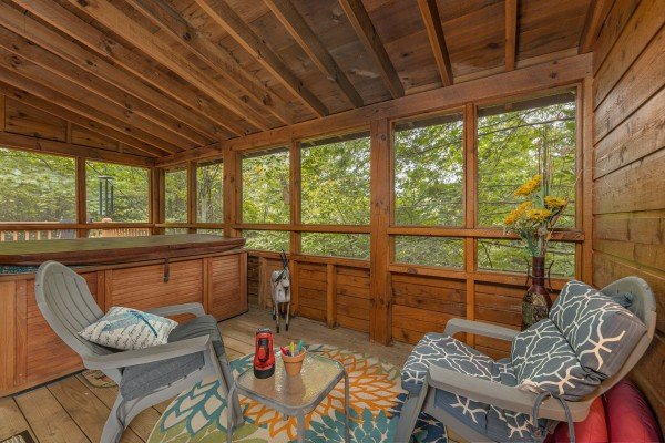 Screened in porch with chairs and a hot tub at Sweet Caroline, a 2 bedroom cabin rental located in Pigeon Forge