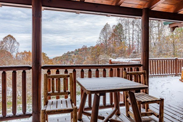 Dining table on a covered deck at Lookout Lodge, a 5 bedroom cabin rental located in Pigeon Forge
