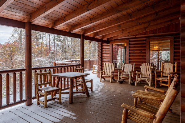 Deck dining table and rocking chairs on a covered porch at Lookout Lodge, a 5 bedroom cabin rental located in Pigeon Forge