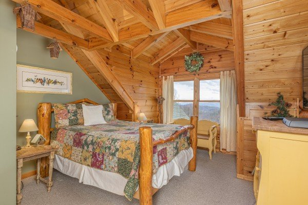 Bedroom with a log bed, tables, and a dresser at Lookout Lodge, a 5 bedroom cabin rental located in Pigeon Forge