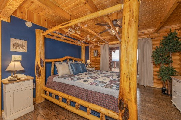 Bedroom with a four post log bed at Lookout Lodge, a 5 bedroom cabin rental located in Pigeon Forge