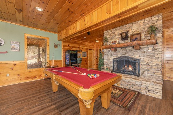 Game room with a red felt pool table and a fireplace at Lookout Lodge, a 5 bedroom cabin rental located in Pigeon Forge
