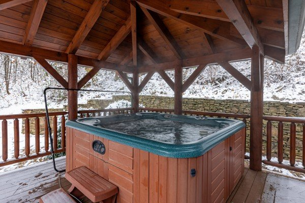 Hot tub on a covered deck at Lookout Lodge, a 5 bedroom cabin rental located in Pigeon Forge