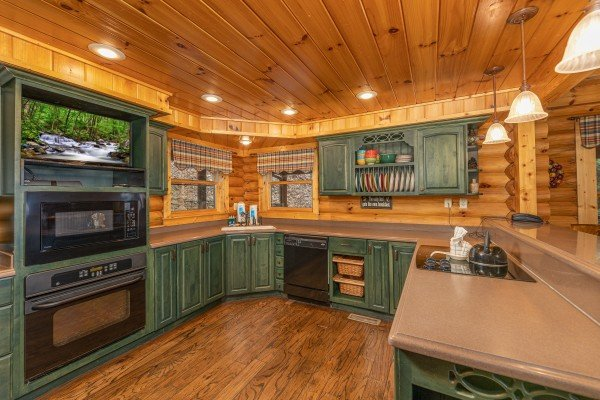 Kitchen with TV and black appliances at Lookout Lodge, a 5 bedroom cabin rental located in Pigeon Forge
