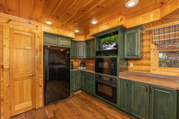 Kitchen with black appliances and a TV at Lookout Lodge, a 5 bedroom cabin rental located in Pigeon Forge
