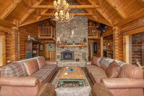Stacked stone fireplace with two antler chandeliers at Lookout Lodge, a 5 bedroom cabin rental located in Pigeon Forge