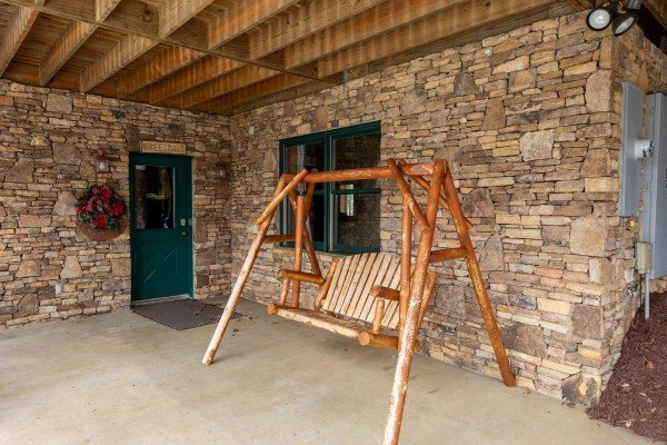 Swing on the lower patio at Lookout Lodge, a 5 bedroom cabin rental located in Pigeon Forge