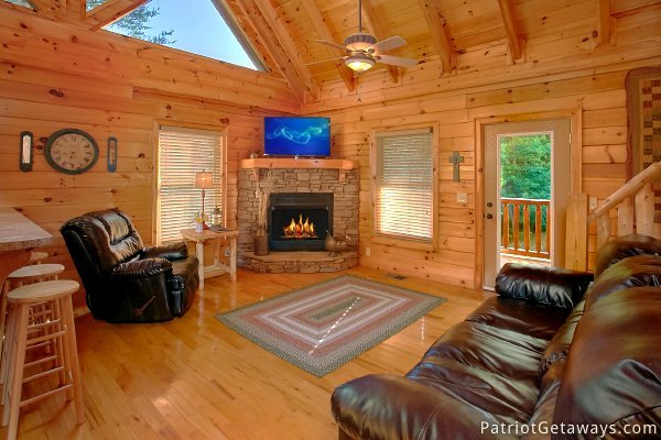 Living room with stone fireplace and leather seating at Alpine Sundance Trail, a 3 bedroom cabin rental located in Pigeon Forge