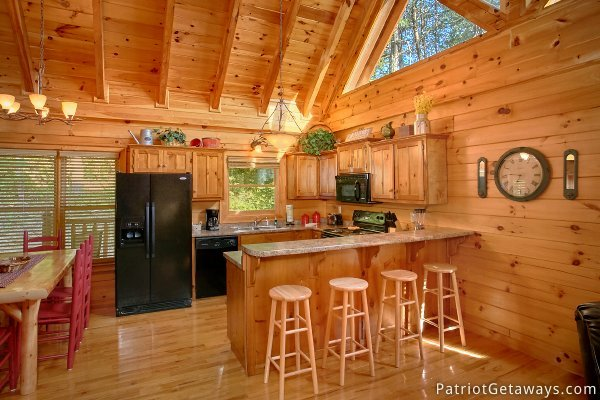 Open layout kitchen with breakfast bar at Alpine Sundance Trail, a 3 bedroom cabin rental located in Pigeon Forge