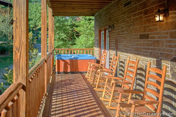 Hot tub and rockers on the deck at Alpine Sundance Trail, a 3 bedroom cabin rental located in Pigeon Forge