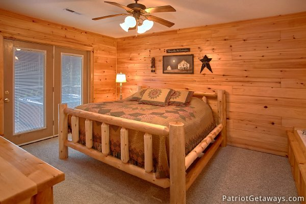 King bed on the second floor with patio doors to deck at Alpine Sundance Trail, a 3 bedroom cabin rental located in Pigeon Forge