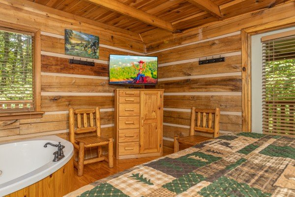 Dresser, TV, and jacuzzi in a bedroom at Bootlegger Hill Hideaway, a 2 bedroom cabin rental located in Pigeon Forge