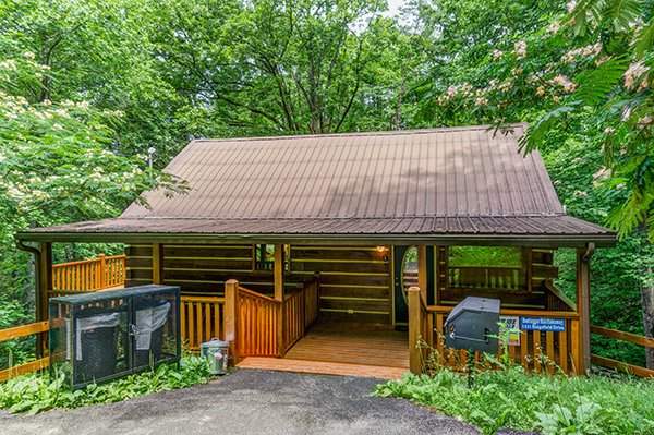Front entry and a charcoal grill at Bootlegger Hill Hideaway, a 2-bedroom cabin rental in Pigeon Forge