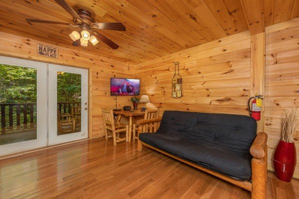 TV, table and chairs, futon, and deck access at Bootlegger Hill Hideaway, a 2 bedroom cabin rental located in Pigeon Forge