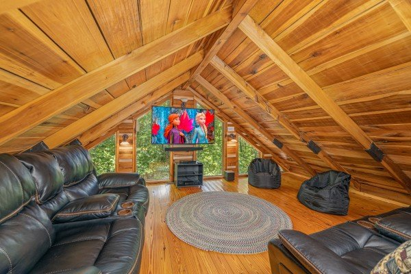 Reclining sofa and TV in the loft space at Bootlegger Hill Hideaway, a 2 bedroom cabin rental located in Pigeon Forge