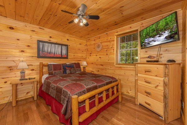Bedroom with a log bed, two night stands, lamps, and a dresser with TV at Bootlegger Hill Hideaway, a 2 bedroom cabin rental located in Pigeon Forge