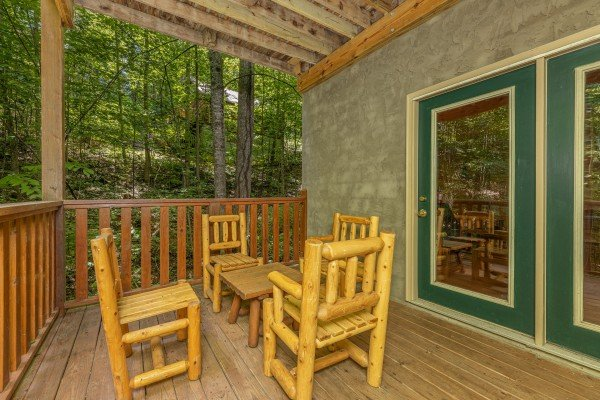 Four log chairs and a table on a deck at Bootlegger Hill Hideaway, a 2 bedroom cabin rental located in Pigeon Forge