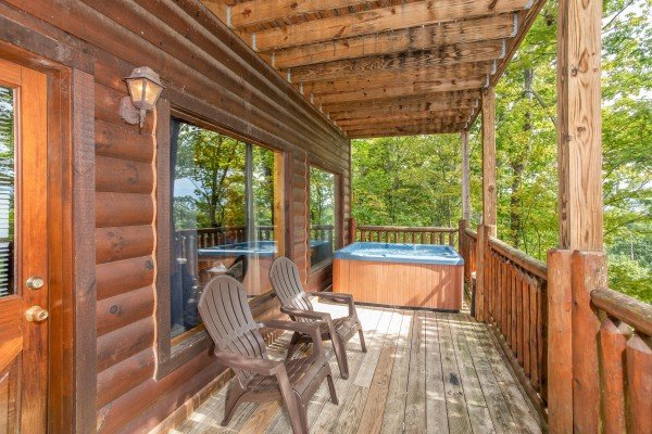 Hot tub and Adirondack chairs on a covered deck at Summit View, a 3 bedroom cabin rental located in Gatlinburg