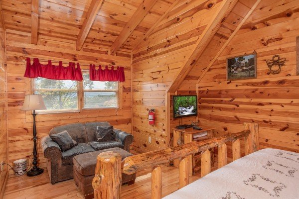 Bedroom with a loveseat and TV at Summit View, a 3 bedroom cabin rental located in Gatlinburg