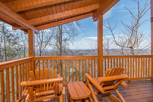 A covered deck and two rocking chairs overlooking the view at Ella-vation, a 3-bedroom cabin rental located in Gatlinburg
