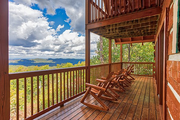 Four rocking chairs on a partially covered deck at Ella-vation, a 3-bedroom cabin rental located in Gatlinburg