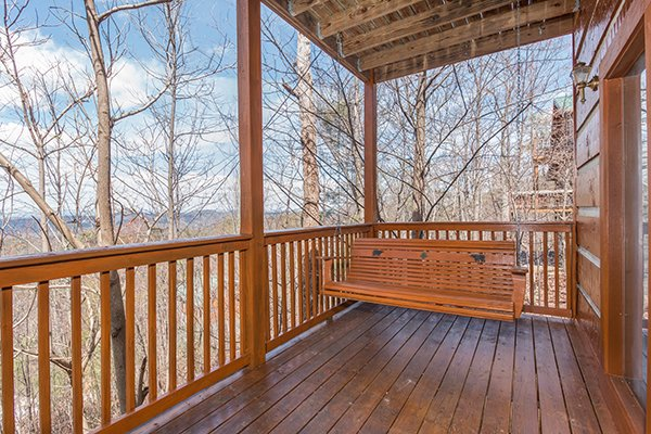 Porch swing on a covered deck at Ella-vation, a 3-bedroom cabin rental located in Gatlinburg