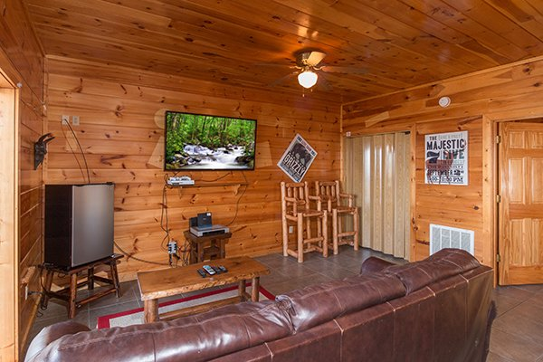 Downstairs living room with a drink fridge, large TV, and game system at Ella-vation, a 3-bedroom cabin rental located in Gatlinburg