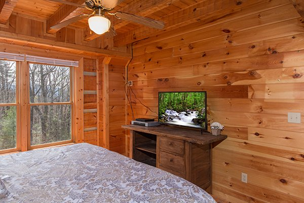 Bedroom with an entertainment console and flat screen TV at Ella-vation, a 3-bedroom cabin rental located in Gatlinburg