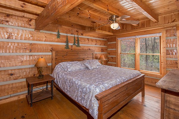 First floor bedroom with a king-sized bed at Ella-vation, a 3-bedroom cabin rental located in Gatlinburg