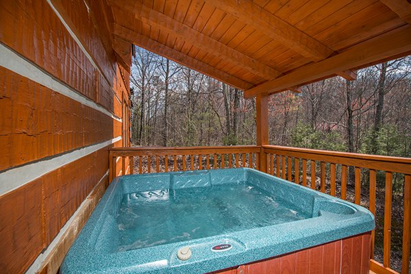 Hot tub on a covered deck surrounded by woods at Ella-vation, a 3-bedroom cabin rental located in Gatlinburg