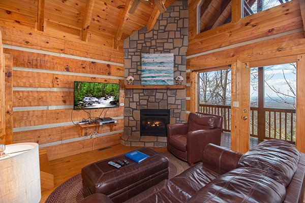 Living room with a tv, fireplace, and deck access at Ella-vation, a 3-bedroom cabin rental located in Gatlinburg