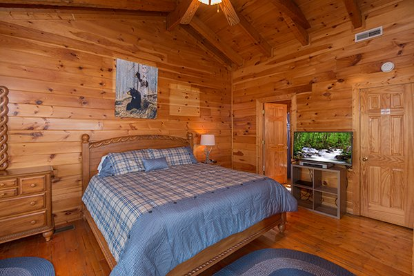 Bedroom with a king-sized bed, large television, and vaulted ceilings at Ella-vation, a 3-bedroom cabin rental located in Gatlinburg