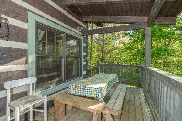Picnic table on a covered deck at Trillium Lodge, a 4 bedroom cabin rental located in Gatlinburg