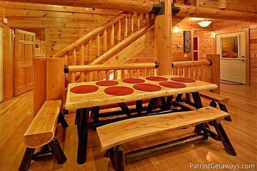 Dining area with custom log benched seating at A Great Escape, a 4-bedroom cabin rental located in Pigeon Forge