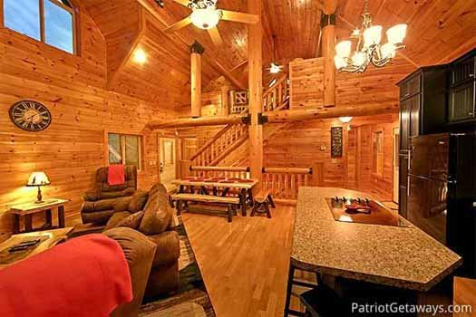 View from the kitchen into the living room and staircases up to lofted bedroom at A Great Escape, a 4-bedroom cabin rental located in Pigeon Forge