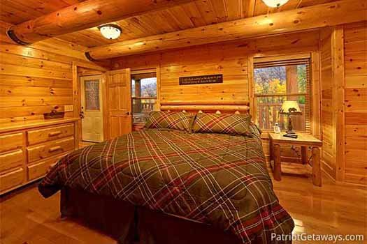 King-sized bed with night stand and dresser at A Great Escape, a 4-bedroom cabin rental located in Pigeon Forge