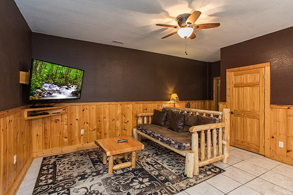 Futon and TV in the game room Corthouse, a 4-bedroom cabin rental located in Pigeon Forge