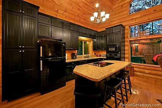 black cabinets and appliances in the kitchen at corthouse a 4 bedroom cabin rental located in pigeon forge