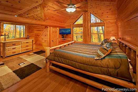 king sized bed and dresser in lofted bedroom at corthouse a 4 bedroom cabin rental located in pigeon forge
