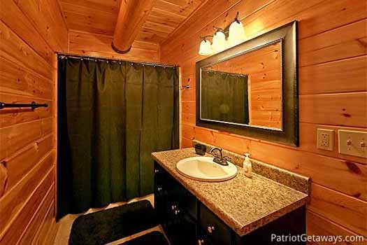 vanity and shower in bathroom attached to bedroom at corthouse a 4 bedroom cabin rental located in pigeon forge